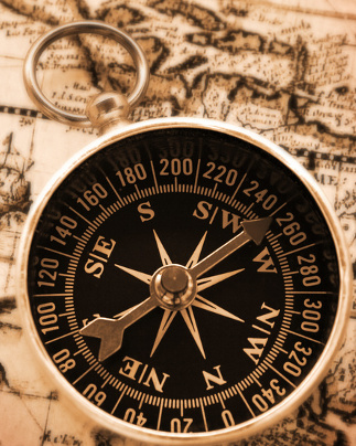 old-fashioned compass on vintage map with warm yellow lighting